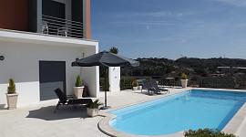 Terras met ligstoelen en zwembad